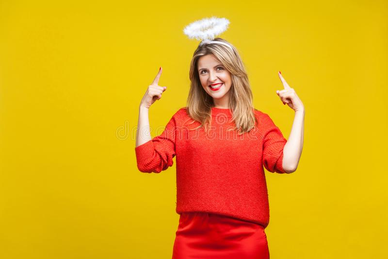 This is me angel! Portrait of proud adorable young woman with bright makeup in red casual clothes, isolated on yellow background stock image