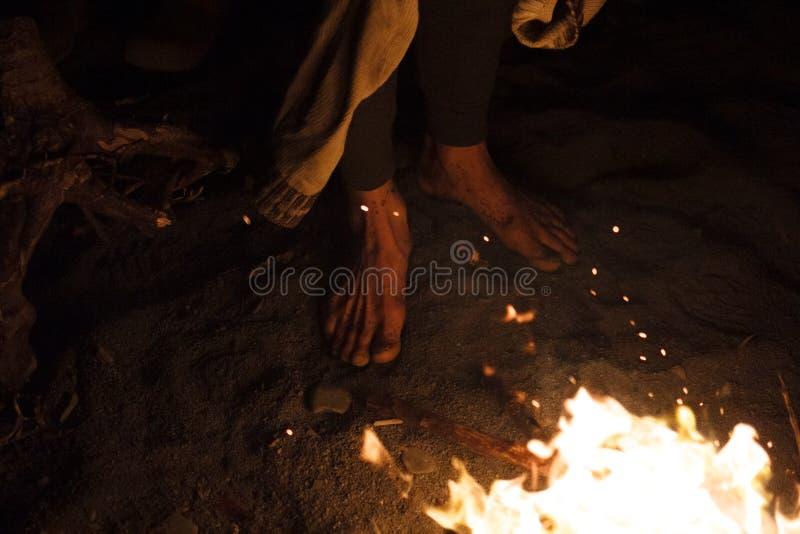 Me caliento los pies por la situación del fuego de la noche en la arena foto de archivo