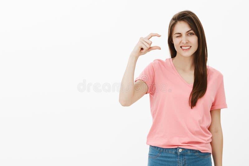 Me costó poco esfuerzo para ganar éxito Retrato de encantar a la mujer hermosa confiada en camiseta rosada, guiñando y fotos de archivo libres de regalías