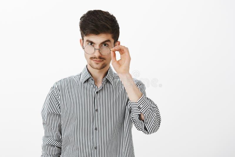 Me intrigan Compañero de trabajo masculino caucásico joven confiado hermoso, mirando de debajo la frente con la ceja levantada fotos de archivo libres de regalías