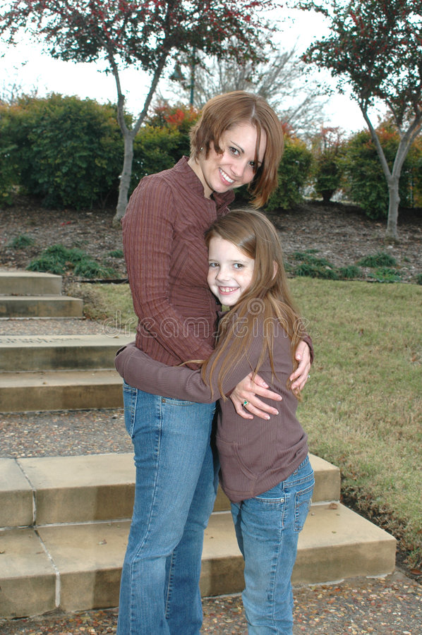 Me and Mom. Beautiful little girl hugging her mother in a park setting royalty free stock images