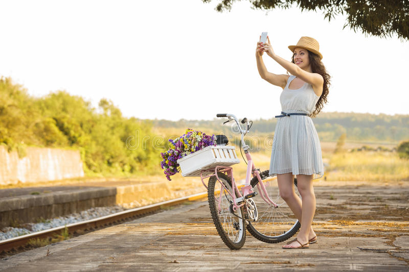 Me and my bike on a selfie. A beautiful young woman with her bicycle and making a selfie royalty free stock photography