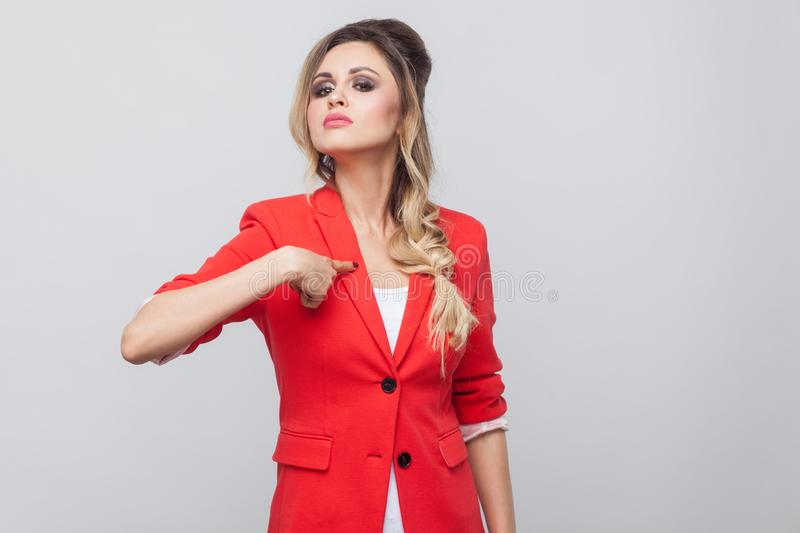 This is me. Portrait of proud beautiful business lady with hairstyle and makeup in red fancy blazer, standing, pointing herself. And looking at camera. indoor stock image