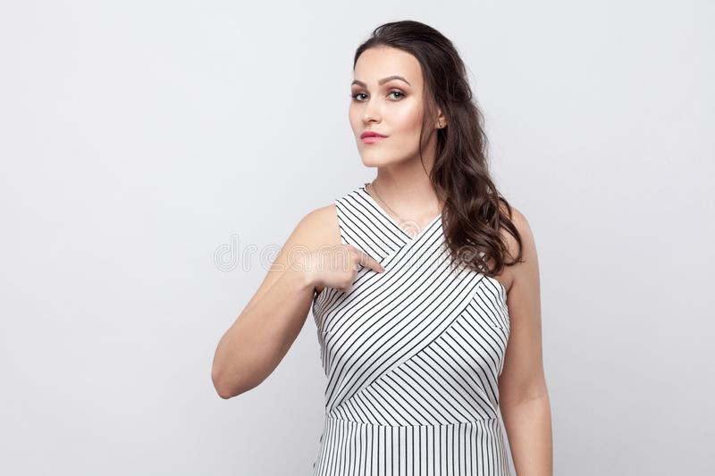 This is me. portrait of proud beautiful young brunette woman with striped dress standing, looking at camera with serious face and stock image