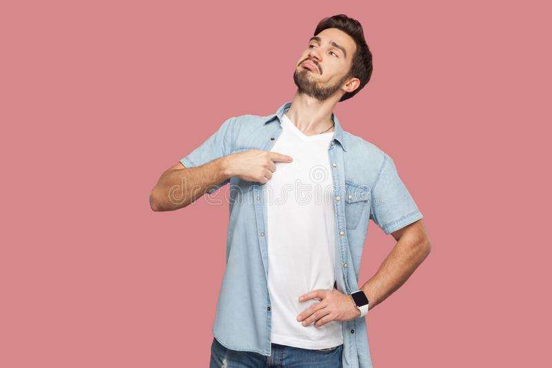 This is me. Portrait of proud haughty handsome bearded young man in blue casual style shirt standing, looking away and pointing. Himself. indoor studio shot royalty free stock photo
