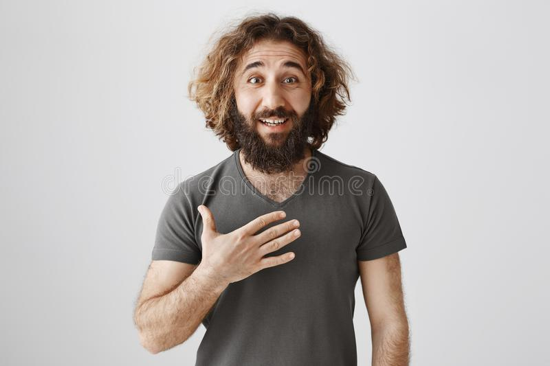 From me to you. Indoor portrait of pleasant handsome eastern male with beard and long curly hair holding palm on chest royalty free stock photos