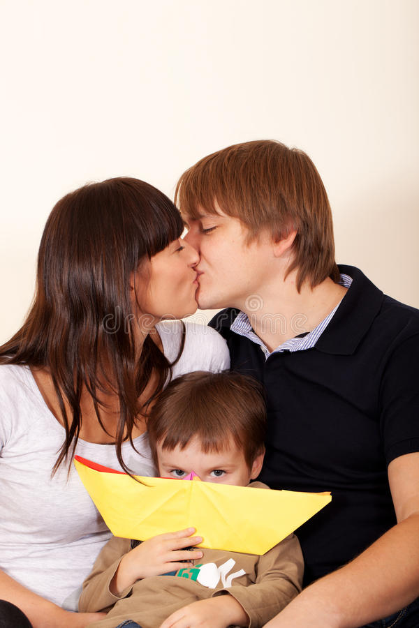 Me too!. Parents are kissing while kid is jealous stock photo