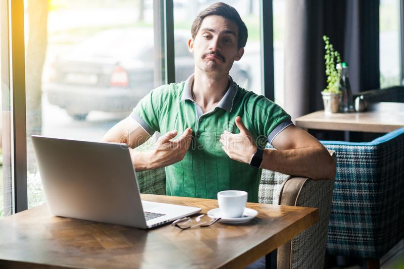 This is me! Young proud haughty businessman in green t-shirt sitting with laptop and looking at camera with proud confident face royalty free stock photo