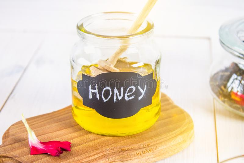 Mead jar labeled honey with a dripper, on a white table. Mead jar labeled honey with a dripper, on a white table stock photos