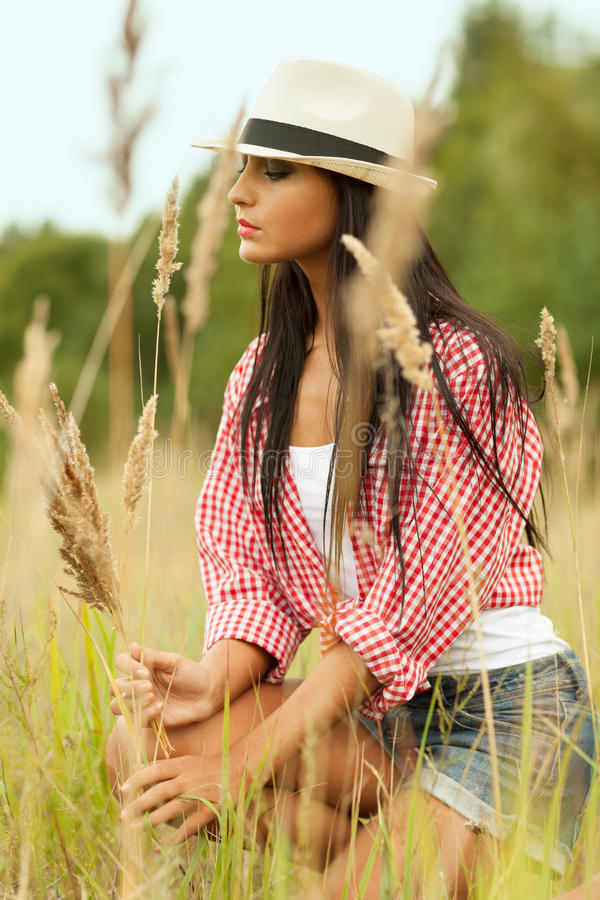 On the meadow. Country girl gathering grass on the meadow royalty free stock image