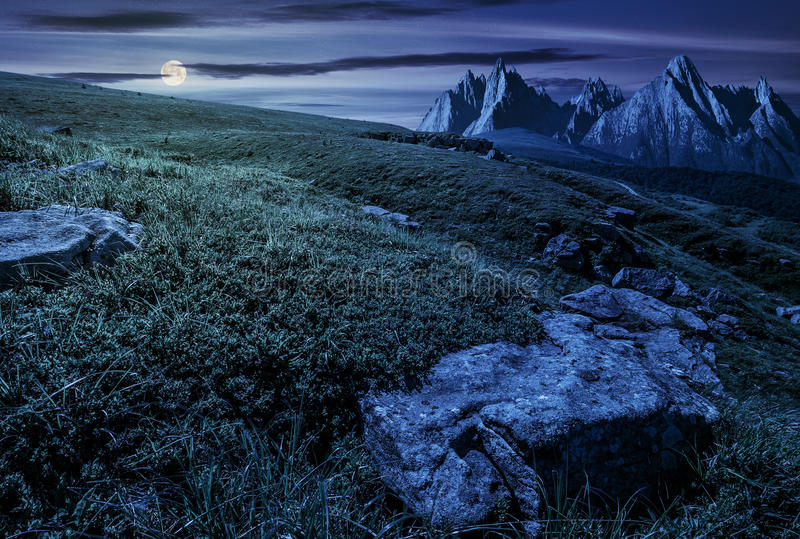 Meadow with huge stones on top of mountain range at night. High Tatra mountain summer landscape at night in full moon light. meadow with huge stones among the stock photography