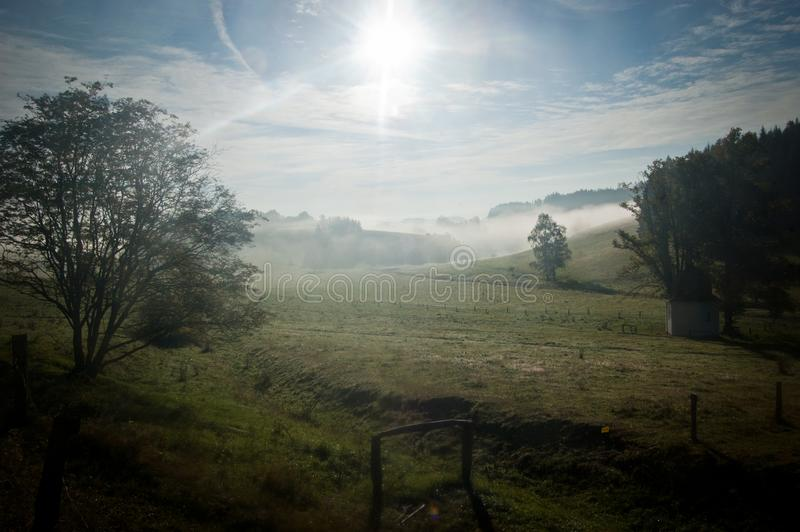 Meadow with a small chapel suffused by sun and haze 2 stock photos