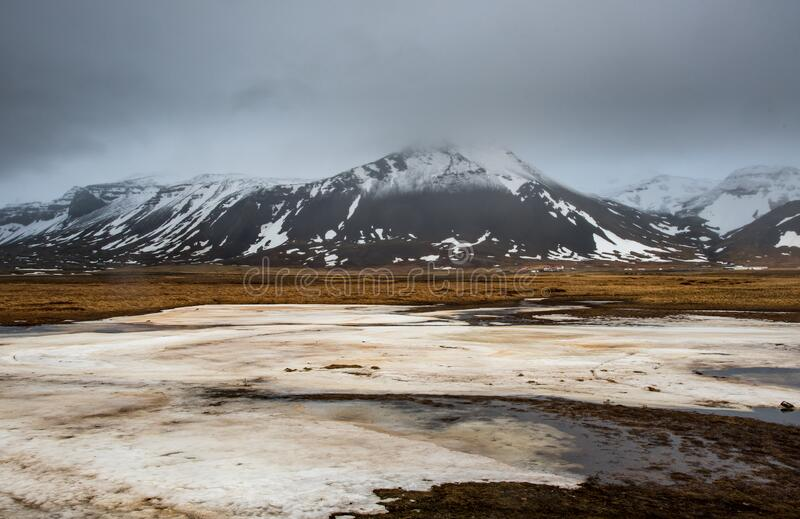 Meadow with snow and frozen lake and snowcapped mountains. Iceland stock photo