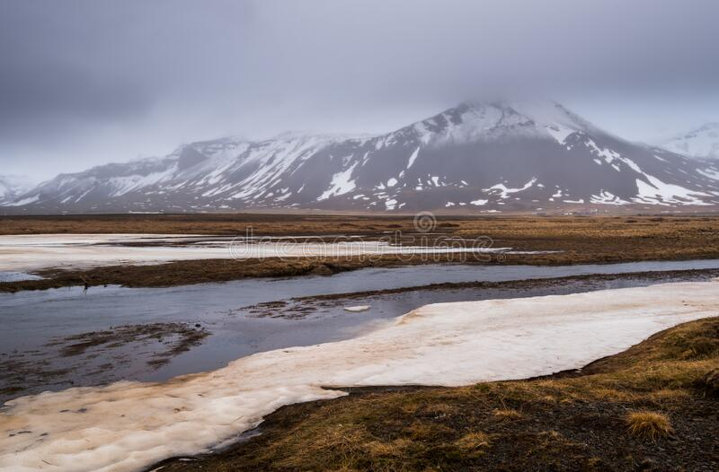 Meadow with snow and frozen lake and snowcapped mountains. Iceland stock image