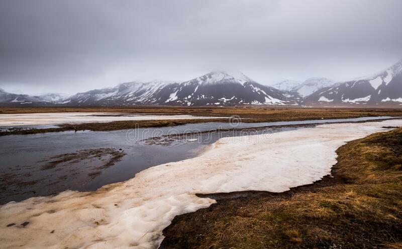 Meadow with snow and frozen lake and snowcapped mountains. Iceland royalty free stock photography