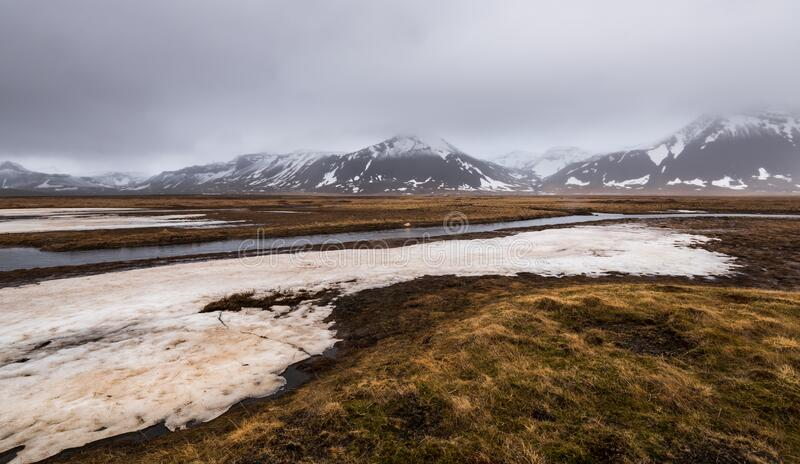 Meadow with snow and frozen lake and snowcapped mountains. Iceland royalty free stock image