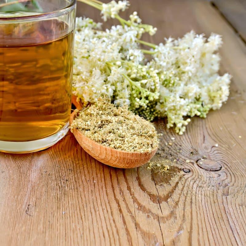 meadowsweet清凉茶在匙子和杯子烘干了 免版税库存图片