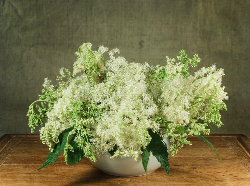 Meadowsweet. Still life. Bouquet of meadow flowers in white pots stock image