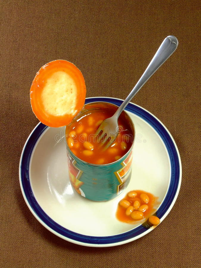 Meal of Baked Beans. An opened tin of baked beans, with fork, sitting on a plate royalty free stock images