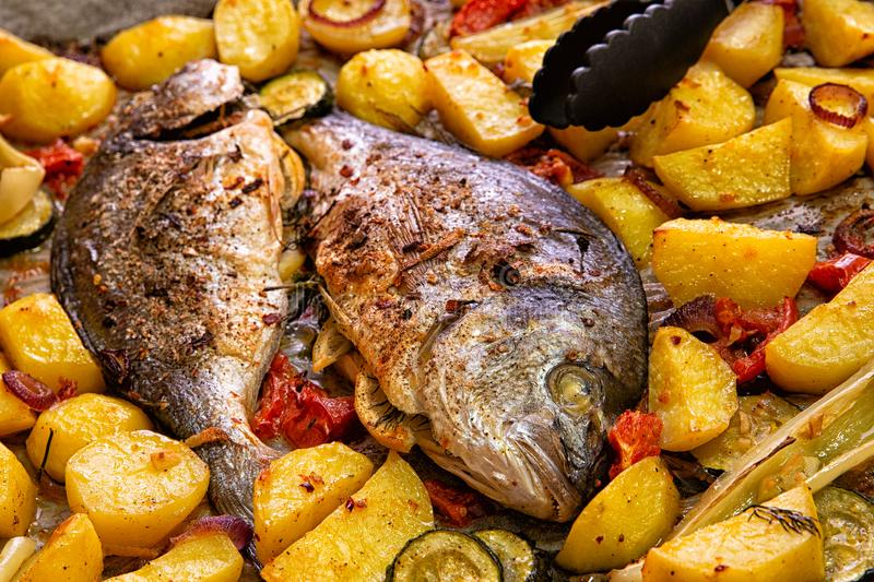 Meal.Baked Dorado fish with vegetables in the oven stock photo