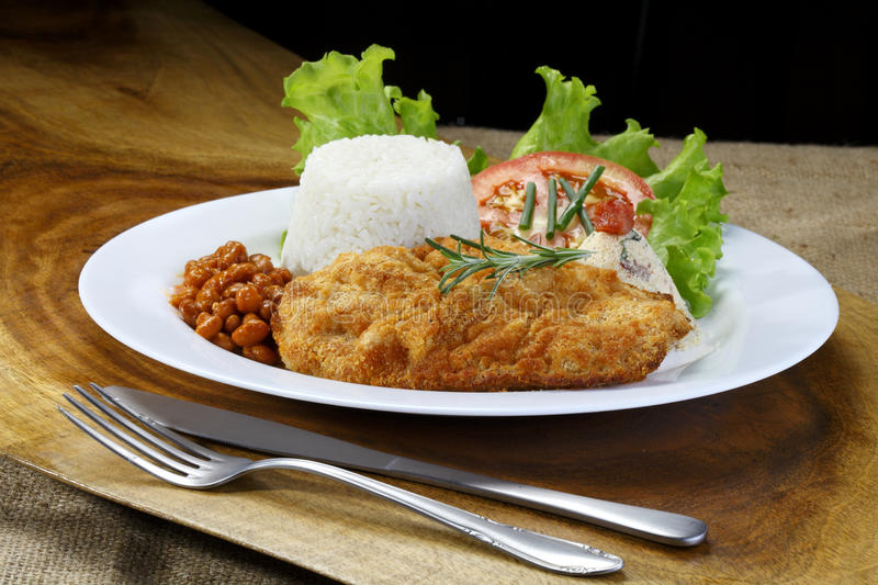 Meal with breaded steak. Breaded steak on a meal served on a dish over a wooden plank royalty free stock image
