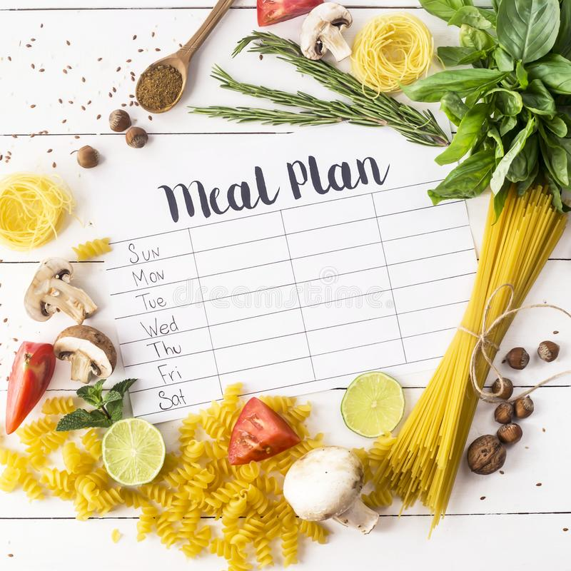 Meal Plan and Products. A meal plan for a week on a white table among products for cooking - pastas, basil, vegetables, lime, seeds, nuts and spices. Top view stock images