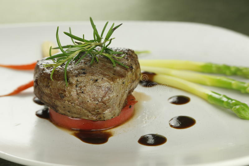 Filet Steak. A meal of rare peppered filet mignon with brown sauce royalty free stock image