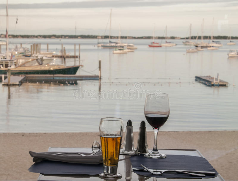 A meal table by the sea. A meal table with a glass of beer and a glass of wine stock image