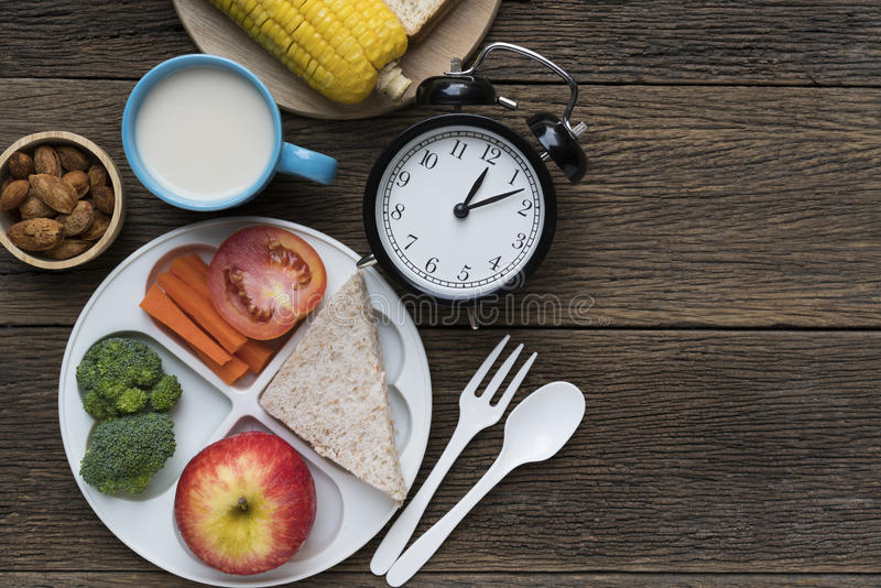Meal time with alarm clock at lunch time stock images