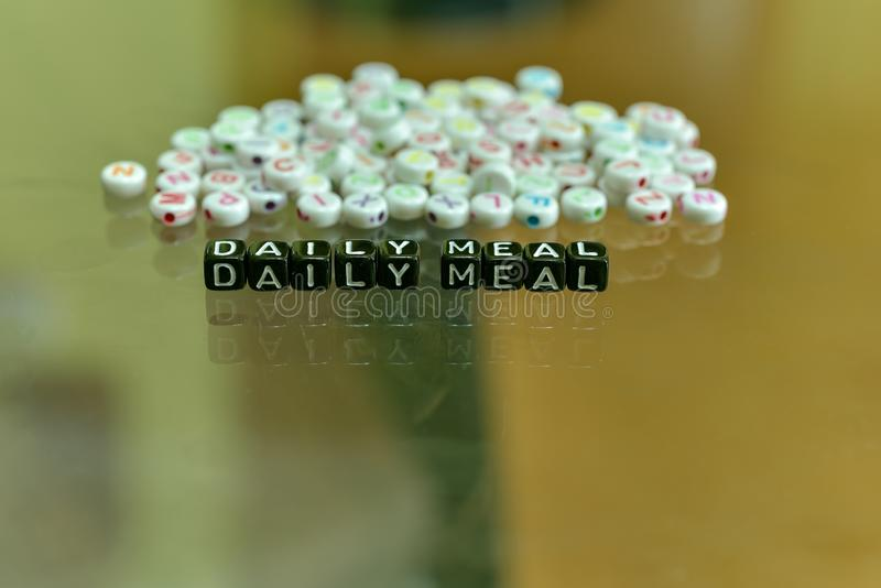 DAILY MEAL  written with Acrylic Black cube with white Alphabet Beads on the Glass Background.  stock photo