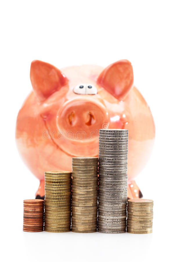 Mealheiro com as pilhas de euro- moedas no fundo branco foto de stock