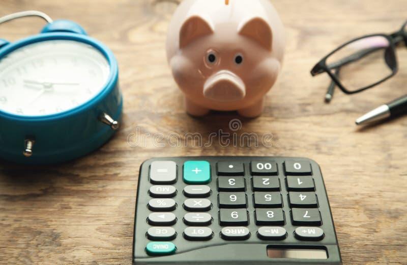Mealheiro com a calculadora na tabela de madeira fotografia de stock royalty free