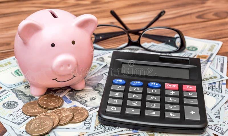 Mealheiro com calculadora, vidros, notas de dólar e moedas na tabela imagem de stock royalty free
