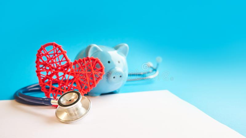 Mealheiro com o estetoscópio no fundo azul conceito do offset do imposto Deduções e reduções de impostos de despesa médica imagens de stock