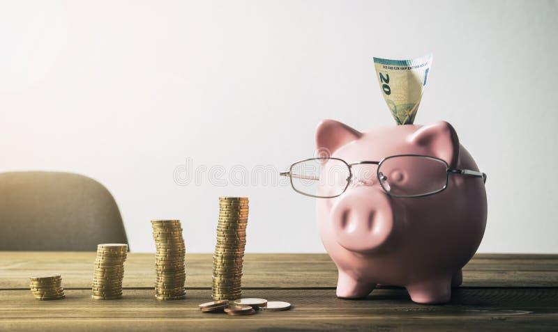 Mealheiro com pilhas da moeda e euro- nota - conceito do aumento imagem de stock