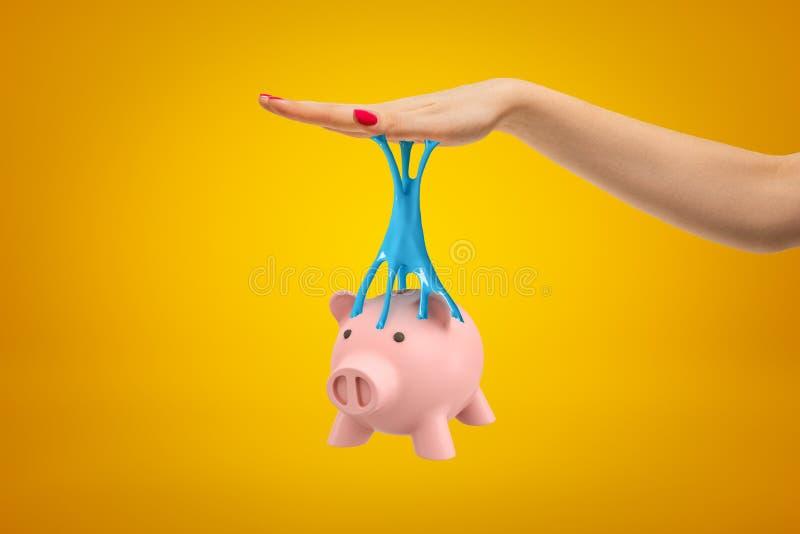 Mealheiro cor-de-rosa colado à mão fêmea com limo pegajoso azul no fundo amarelo imagem de stock royalty free