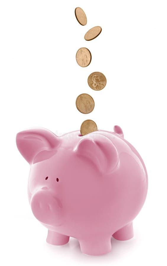 Mealheiro cor-de-rosa com as moedas de ouro de queda imagem de stock