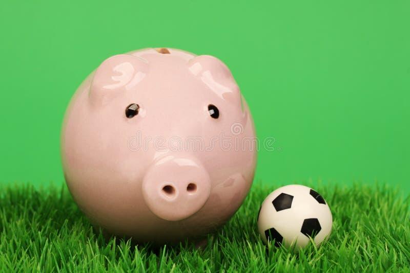 Mealheiro cor-de-rosa com bola de futebol em um passo da grama fotografia de stock royalty free