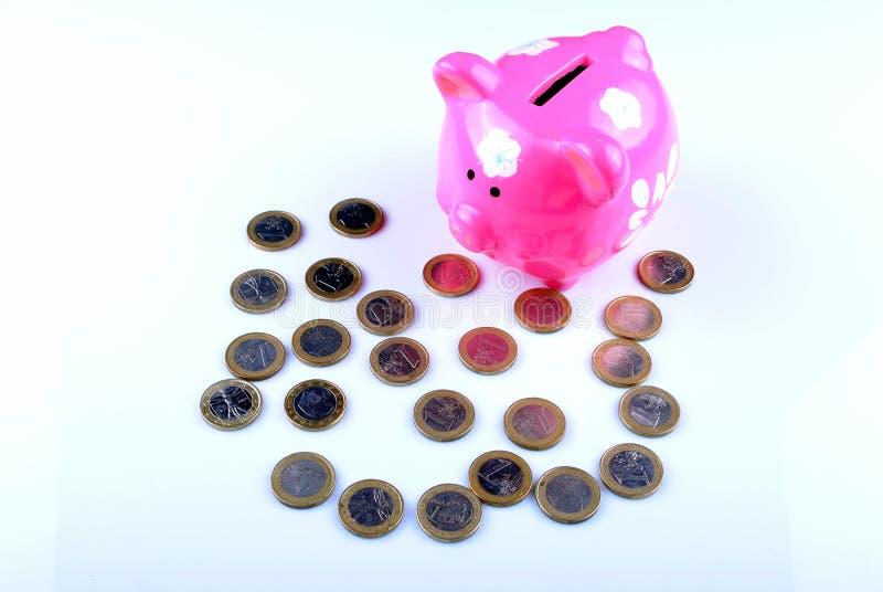 Mealheiro cor-de-rosa com euro- moedas fotos de stock royalty free