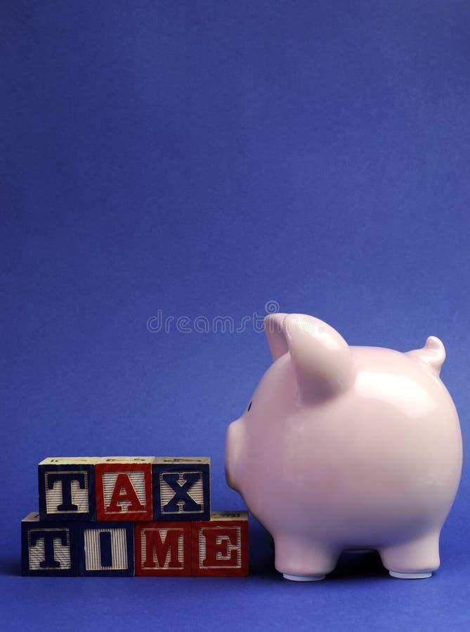 Mealheiro cor-de-rosa com mensagem do tempo do imposto em blocos de apartamentos para o dia do imposto ou o fim do exercício orçam imagens de stock