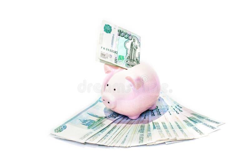 Mealheiro cor-de-rosa com uma cédula introduzida no entalhe em um planeamento financeiro, em economias e em conceito do investime foto de stock