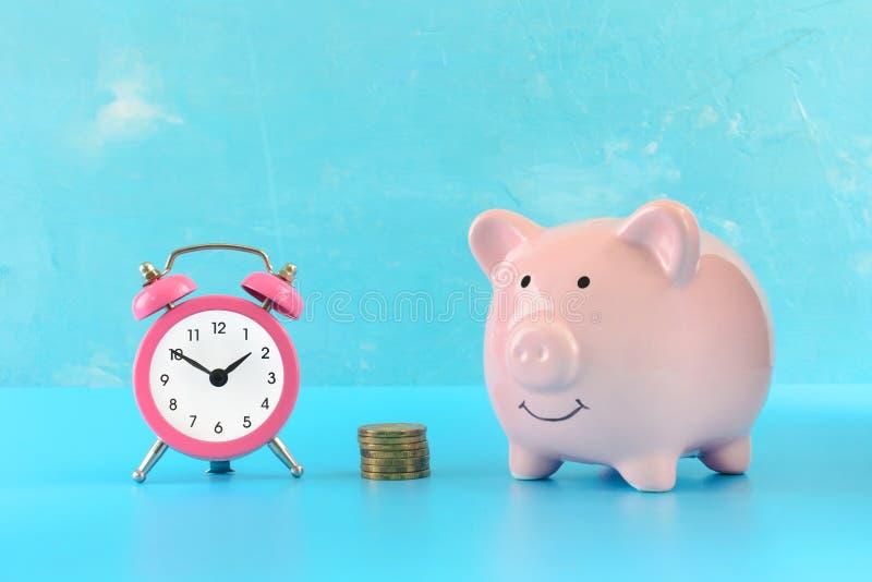 Mealheiro cor-de-rosa em um fundo de turquesa Ao lado de uma pilha de moedas e de um despertador cor-de-rosa pequeno Retrato bril imagens de stock