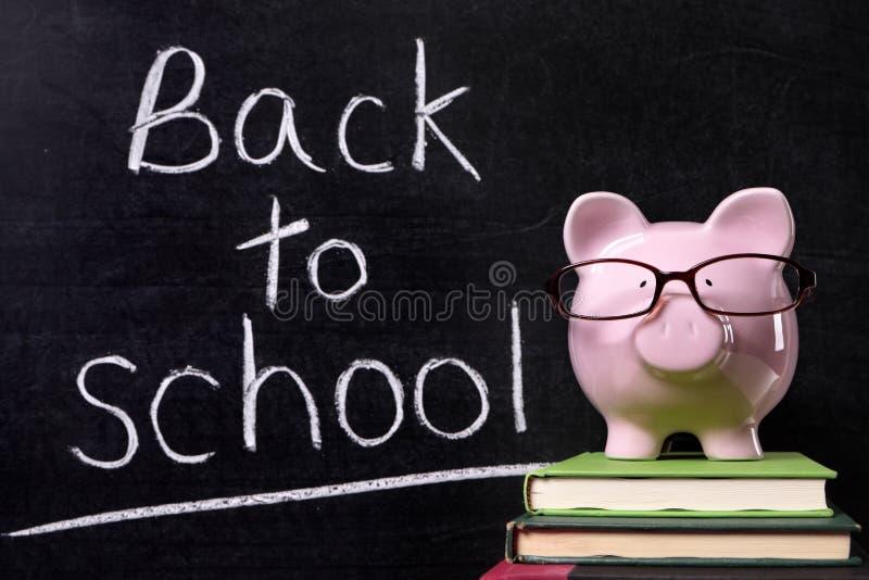 Mealheiro de volta à mensagem da escola, conceito dos custos de educação imagem de stock
