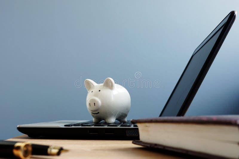 Mealheiro em um portátil Economias ou conceito em linha da operação bancária fotos de stock