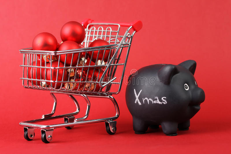 Mealheiro preto com Xmas branco do texto e o cesto de compras completo de bolas matt e lustrosas vermelhas do Natal no fundo verm imagem de stock