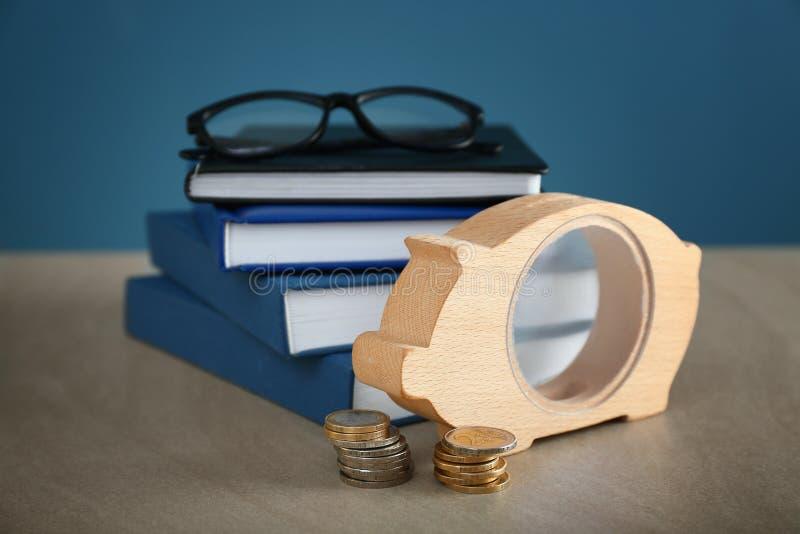 Mealheiro, vidros e pilha de livros na tabela Conceito das economias para a educação imagem de stock