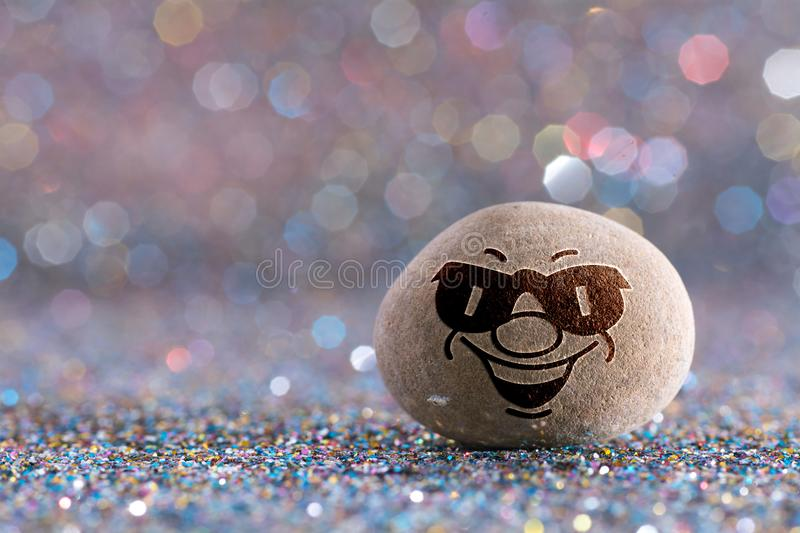 The mean stone emoji. Emotions on color glitter boke background royalty free stock photos