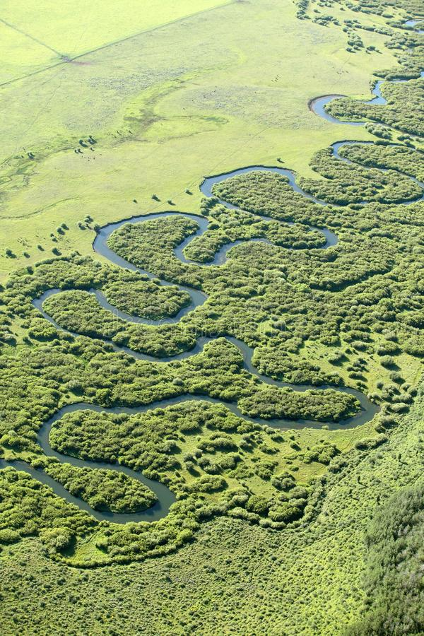 A meandering stream twisting an turning through a flat meadow. royalty free stock photos