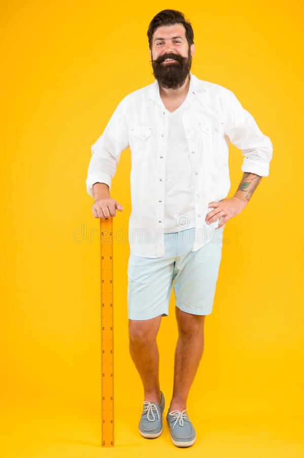 Measure. Geometry theorem. Actual size. School teacher. Small little big large. Does size really matter. One meter. Man. Bearded hipster holding ruler. Measure royalty free stock images