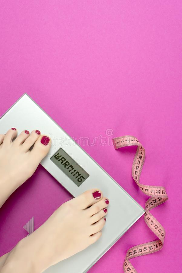 Measure tape and scales on a pink background with the words warning. Diet plan and workout women before the summer season. Healthy stock image